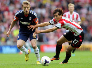 Photo - Sunderland's Ji Dong-Won, right, vies for the ball with Fulham's Damien Duff, left, during their English Premier League soccer match at the Stadium of Light, Sunderland, England, Saturday, Aug. 17, 2013. (AP Photo/Scott Heppell)