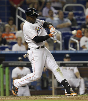 Photo - Miami Marlins' Marcell Ozuna connects a single against the Philadelphia Phillies in the fourth inning of a baseball game in Miami, Wednesday, May 21, 2014. Garrett Jones scored on the base hit. (AP Photo/Alan Diaz)