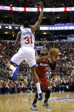 Photo - Miami Heat's Dwyane Wade (3) prepares to shoot against Philadelphia 76ers' Hollis Thompson (31) during the first half of an NBA basketball game on Friday, Jan. 17, 2014, in Philadelphia. (AP Photo/Matt Slocum)