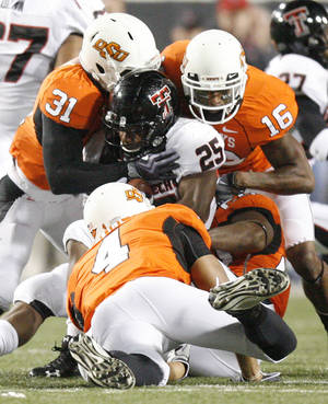 Photo - Cowboys Lucien Antoine (31) Patrick Levine (4) and Perrish Cox (16) stop Baron Batch (25) during the college football game between Oklahoma State University (OSU) and Texas Tech University (TT) at Boone Pickens Stadium in Stillwater, Okla. Photo by Sarah Phipps, The Oklahoman