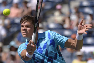 Photo - Milos Raonic, of Canada, returns a volley against Andy Murray, of Great Britain, during a fourth round match at the BNP Paribas Open tennis tournament, Wednesday, March 12, 2014, in Indian Wells, Calif. (AP Photo/Mark J. Terrill)