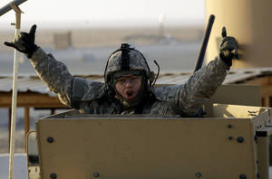 Photo -   A soldier gestures from the gun turret of the last vehicle in a convoy of the US Army's 3rd Brigade, 1st Cavalry Division crosses the border from Iraq into Kuwait, Sunday, Dec. 18, 2011. The brigade's special troops battalion are the last American soldiers to leave Iraq. (AP Photo/Maya Alleruzzo)
