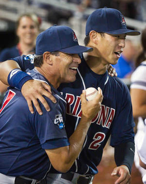 photo -   Arizona head coach Andy Lopez, left, gets a ball from Robert Refsnyder following their 4-1 victory over South Carolina in Game 2 to win the NCAA College World Series baseball finals in Omaha, Neb., Monday, June 25, 2012. (AP Photo/The Omaha World-Herald/Jeff Beiermann) MAGS OUT TV OUT