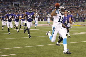 Photo - Carolina Panthers' Ted Ginn leaves a trail of Baltimore Ravens as he runs to the end zone for a touchdown on a 74-yard punt return during the first half of a preseason NFL football game in Baltimore, Thursday, Aug. 22, 2013. (AP Photo/Nick Wass)
