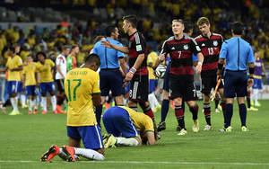 Photo - Brazil players sink to their knees after the World Cup semifinal soccer match between Brazil and Germany at the Mineirao Stadium in Belo Horizonte, Brazil, Tuesday, July 8, 2014. Germany won the match 7-1. (AP Photo/Martin Meissner)