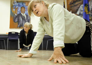 photo - Margie Warrix looks up during a boot camp workout session Thursday night at Ralph Ellison Library.  Photo by Bryan Terry, The Oklahoman