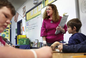 Photo - Sallie Harrison teaches a lesson in long division to her fourth-grade students. Harrison has has multiple sclerosis.    Photo by Jim Beckel, The Oklahoman <strong>Jim Beckel - THE OKLAHOMAN</strong>