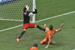 Photo - Mexico's goalkeeper Guillermo Ochoa makes a save after a shot by Netherlands' Klaas-Jan Huntelaar during the World Cup round of 16 soccer match between the Netherlands and Mexico at the Arena Castelao in Fortaleza, Brazil, Sunday, June 29, 2014. (AP Photo/Themba Hadebe)