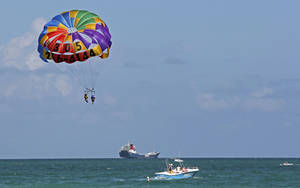 Photo -   In this Sept. 24, 2012 photo, two people parasail over the Miami Beach,Fla. area. Soaring high above the ocean off South Beach, tethered only by a rope to a boat hundreds of feet below, riding in a parasail is at once exhilarating and oddly peaceful, even quiet. For millions of people, that's the takeaway from a once-in-a-lifetime experience. But every year there are accidents, some of them fatal. The Parasail Safety Council, which tracks injuries and deaths from the activity nationwide, reports more than 70 people have been killed and at least 1,600 injured between 1982 and 2012, out of an estimated 150 million parasail rides during those 30 years. Despite the inherent risk, few federal or state safety regulations exist for parasailing. In Florida, which has by far the largest number of parasail operators at about 120, repeated efforts to enact new rules following fatal accidents have landed with a thud. Florida is seen by safety proponents as a national bellwether because of parasailing's popularity in the state. (AP Photo/Tony Winton)