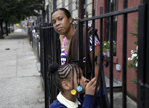 Photo -   Olgita Blackwood, top, waits for her son to return home from school with her daughter, Malaysia Blackwood, 7, at their apartment in the Drew House in New York, Wednesday, Oct. 3, 2012. The program, called Drew House, is one of a kind in the nation, where mothers arrested on felonies can live with their children, instead of in prison. The program has been lauded as a success that should be replicated around the country, but the small house is already full, and without additional funding and space, it can't grow. (AP Photo/Seth Wenig)