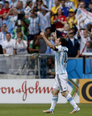 Photo - Argentina's Lionel Messi celebrates after scoring his side's first goal during the group F World Cup soccer match against Nigeria at the Estadio Beira-Rio in Porto Alegre, Brazil, Wednesday, June 25, 2014. (AP Photo/Martin Meissner)(AP Photo/Jon Super)