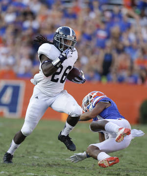 Photo - Georgia Southern wide receiver Tray Butler (26) runs past Florida defensive back Cody Riggs during the second half of an NCAA college football game in Gainesville, Fla., Saturday, Nov. 23, 2013.(AP Photo/John Raoux)