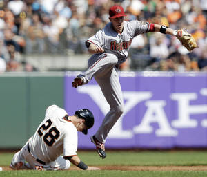 Photo -   Arizona Diamondbacks second baseman Aaron Hill watches his throw to first after forcing out San Francisco Giants' Buster Posey on a ground ball by Hunter Pence during the third inning of a baseball game Thursday, Sept. 27, 2012, in San Francisco. Pence was out at first. (AP Photo/Marcio Jose Sanchez)