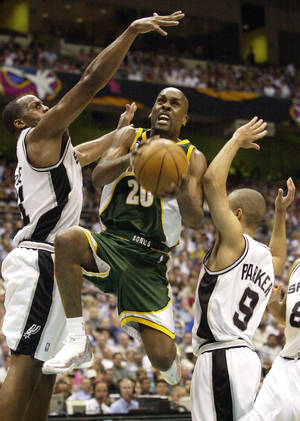 Photo - NBA BASKETBALL PLAYOFFS: Seattle SuperSonics guard Gary Payton (20) goes to the basket as  San Antonio Spurs' Malik Rose, left, and Tony Parker defend during the third quarter of their first-round playoff game in San Antonio, Monday, April 22, 2002. (AP Photo/Eric Gay)