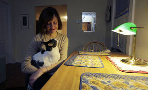 photo - Valerie Spain poses with her pet cat at the kitchen table of her Cambridge, Mass., home, Thursday, Jan. 17, 2013.  The 57-year-old former operations manager was able to find insurance through the subsidized Commonwealth Care program created under the a Massachusetts healthcare law. She pays no premiums, but is charged a $20 co-pay for visits to her doctor's office. (AP Photo/Charles Krupa)