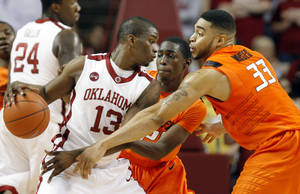 Photo - OSU's Marshall Moses, right, and Fred Gulley defend OU guard Willie Warren during the Sooners' 62-57 win Monday at the Lloyd Noble Center in Norman. PHOTO BY CHRIS LANDSBERGER, THE OKLAHOMAN