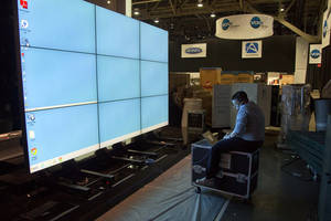 photo - Sharp Electronics employee Michael Nenortas programs a flat screen display at the company's booth for the International Consumer Electronics Show, Sunday, Jan. 6, 2013, in Las Vegas. The show, which drew more than 3,100 exhibitors in 2012 and is open only to industry affiliates, begins Tuesday and runs through Friday. (AP Photo/Julie Jacobson)