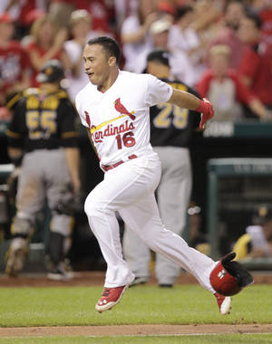 Photo - St. Louis Cardinals' Kolten Wong (16) tosses his helmet as he approaches home plate after hitting a walk-off home run, as Pittsburgh Pirates catcher Russell Martin (55) and relief pitcher Ernesto Frieri (29) head for the dugout in the ninth inning of a baseball game, Tuesday, July 8, 2014 in St. Louis. The Cardinals beat the Pirates 5-4. (AP Photo/Tom Gannam)