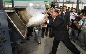 Photo -   FILE - In this April 26, 2012 file photo, Interior Minister Daniel Lozada throws a bag of seized cocaine into an incinerator at a police base in Lima, Peru. Peru's defense and interior ministers have quit amid complaints from lawmakers about incompetence in the fight against Shining Path rebels. (AP Photo/Karel Navarro, File)