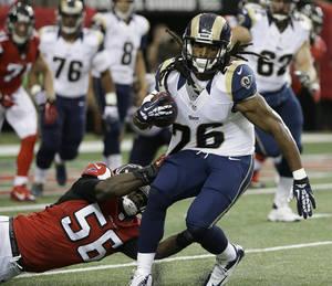 Photo - St. Louis Rams running back Daryl Richardson (26) is hit by Atlanta Falcons outside linebacker Sean Weatherspoon (56) during the first half of an NFL football game, Sunday, Sept. 15, 2013, in Atlanta. (AP Photo/David Goldman)