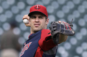 Photo - Minnesota Twins' Joe Mauer throws before a baseball game against the Detroit Tigers in Detroit, Tuesday, Aug. 20, 2013. Mauer was scratched from the lineup against the Tigers because he experienced dizziness Tuesday night in batting practice. (AP Photo/Paul Sancya)