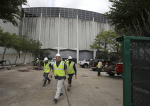 Photo - Construction workers walk out a gate outside an Astrodome loading area Tuesday, Nov. 5, 2013, in Houston. Voters are deciding whether to approve a referendum authorizing up to $217 million in bonds to turn the stadium that once hosted both baseball and football games into a giant convention center and exhibition space. (AP Photo/Pat Sullivan)