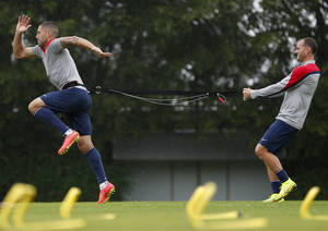 Photo - United States' Clint Dempsey, left, and Brad Davis work on resistance exercises during a training session at the Sao Paulo FC training center in Sao Paulo, Brazil, Tuesday, June 10, 2014. The U.S. will play in group G of the 2014 soccer World Cup. (AP Photo/Julio Cortez)