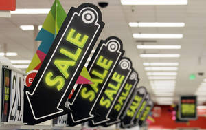 photo - Sale signs are displayed at a Target store in Colma, Calif. Big retailers, from Best Buy to Target to Toys R Us, are engaging in a price war this holiday season, and shoppers can score some good deals if they know how to navigate them. But what's different this holiday season is that Best Buy and Target are matching online retailers such as Amazon.com for the first time. That's a big deal, since online prices tend to be lower than those in the store. AP Photo <strong>Jeff Chiu</strong>
