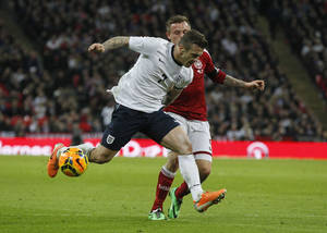 Photo - England's Jack Wilshere, front, competes with Denmark's Peter Ankersen during the international friendly soccer match between England and Denmark at Wembley Stadium in London, Wednesday, March 5, 2014. (AP Photo/Sang Tan)
