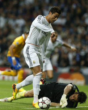 Photo - Real's Cristiano Ronaldo takes the ball past Juventus goalkeeper Gianluigi Buffon before scoring his side's first goal during a Group B Champions League soccer match between Real Madrid and Juventus at the Santiago Bernabeu stadium in Madrid, Spain, Wednesday Oct. 23, 2013. (AP Photo/Andres Kudacki)