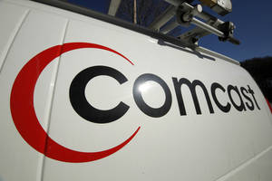 Photo - FILE - This Feb. 11, 2011 file photo shows the Comcast logo on one of the company's vehicles, in Pittsburgh. Comcast has agreed to buy Time Warner Cable for $45.2 billion in stock, or $158.82 per share, in a deal that would combine the top two cable TV companies in the nation, according to a person familiar with the matter who spoke on condition of anonymity because it had not been announced formally. An announcement is set for Thursday morning, Feb. 13, 2014, the person said. (AP Photo/Gene J. Puskar, File)