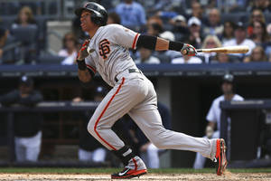 Photo - San Francisco Giants' Ehire Adrianza (53) hits a solo home run in the sixth inning of a baseball game against the New York Yankees at Yankee Stadium, Sunday, Sept. 22, 2013, in New York. The Giants defeated the Yankees, 2-1. (AP Photo/John Minchillo)