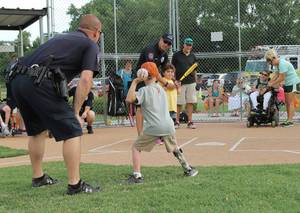 Photo -  Yukon police department members provide guidance as kids participate in the Yukon Spirit Baseball League. The league for special needs children has wrapped up its season. The league is sponsored by the Yukon police and fire departments and the parks and recreation department. PHOTO PROVIDED  <strong>PROVIDED</strong>