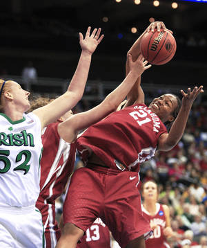 Photo - Oklahoma's Amanda Thompson, right, pulls down a rebound in front of Notre Dame's Erica Williamson during a Kansas City Regional semifinal game on March 28. Thompson had 14 rebounds in the game. AP Photo