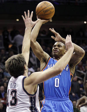 photo - Oklahoma City Thunder's Russell Westbrook (0) shoots past New Jersey Nets' Mehmet Okur (13), of Turkey, during the third quarter of an NBA basketball game in Newark, N.J., Saturday, Jan. 21, 2012. Westbrook contributed 21 points as the Thunder won 84-74. (AP Photo/Mel Evans) ORG XMIT: NJME122