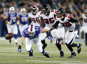Photo - Buffalo Bills tight end Scott Chandler (84) fumbles the ball in front of Atlanta Falcons defenders William Moore (25) and Thomas DeCoud (28) during overtime in an NFL football game on Sunday, Dec. 1, 2013, in Toronto. Atlanta recovered on the play and won 34-31. (AP Photo/Gary Wiepert)