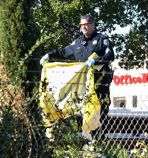 Photo - A BART police officer covers one of the two people that were struck and killed by a moving BART train along Jones Road in Walnut Creek, Calif., on Saturday, Oct. 19, 2013. (AP Photo/The Mercury News, Dan Rosenstrauch)