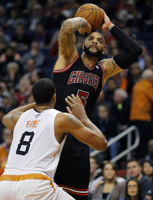 Photo - Chicago Bulls' Carlos Boozer (5) shoots over Phoenix Suns' Channing Frye (8) during the first half of an NBA basketball game, Tuesday, Feb. 4, 2014, in Phoenix. (AP Photo/Matt York)