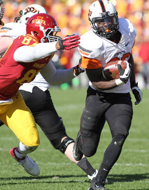 Photo - Oklahoma State running back Desmond Roland (26) breaks away from Iowa State defensive lineman David Irving (86) during the second half of an NCAA college football game in Ames, Iowa Saturday, Oct. 26, 2013. Oklahoma State won the game 58-27.(AP Photo by Justin Hayworth)