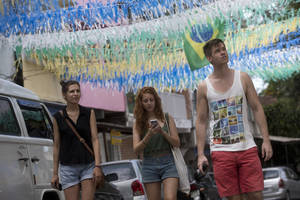Photo - In this May 23, 2014, photo, tourists walk on a street decorated for the upcoming World Cup, in Rio de Janeiro, Brazil. Visitors to Brazil will find the land of soccer, sun and surprisingly sky-high prices. It's not just hotels and flights that are wallet busters. It's the $35 pepperoni pizza, the $10 cocktails and $17 cheeseburgers, standard prices around the country. (AP Photo/Silvia Izquierdo)