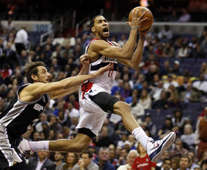 Photo - Washington Wizards guard Garrett Temple (17) drives past San Antonio Spurs guard Marco Belinelli (3), from Italy, in the first half of an NBA basketball game on Wednesday, Feb. 5, 2014, in Washington. (AP Photo/Alex Brandon)