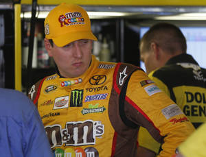 Photo - Driver Kyle Busch talks with crew members during practice for Sunday's NASCAR Sprint Cup series auto race at Kansas Speedway in Kansas City, Kan., Friday, Oct. 4, 2013. (AP Photo/Orlin Wagner)