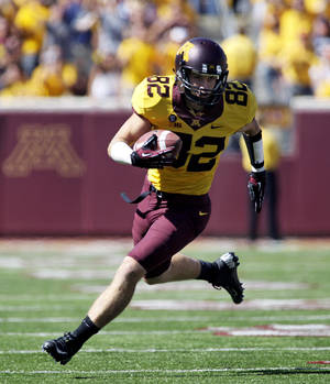 Photo -   Minnesota wide receiver A.J. Barker (82) heads to the end zone on a 53 yard touchdown catch and run during the first half of an NCAA football game, Saturday, Sept. 15, 2012, in Minneapolis. Minnesota won 28-23. Barker finished with 101 yards and three touchdowns. (AP Photo/Paul Battaglia)