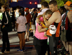 photo - Bret and Angie Sholar embrace during 168 seconds of silence before the Oklahoma City Memorial Marathon in Oklahoma City, Sunday, April 29, 2012. Photo by Bryan Terry, The Oklahoman
