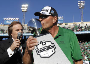 Photo - North Texas head coach Dan McCarney kisses the Heart of Dallas Bowl trophy following their 36-14 win over UNLV in the Heart of Dallas NCAA college football game, Wednesday, Jan. 1, 2014, in Dallas. (AP Photo/Mike Stone)