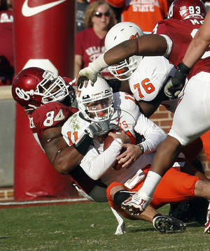 Photo - Oklahoma State quarterback Zac Robinson, center, is sacked by Oklahoma defensive end Frank Alexander, left, in the fourth quarter of an NCAA college football game in Norman, Okla., Saturday, Nov. 28, 2009. AP Photo