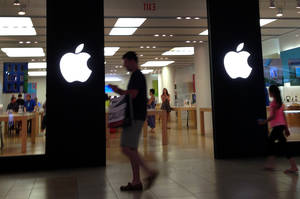 Photo - A shopper walks by an Apple store in Peabody, Mass., Monday, June 9, 2014. Apple's resurgent stock may have as much to do with financial engineering as the company's technological wizardry. In late April, the iPhone and iPad maker announced plans to split its stock for the first time in nine years. Since then, Apple's stock has climbed 23 percent, creating more than $100 billion in shareholder wealth while the Standard & Poor's 500 edged up just 4 percent. (AP Photo/Elise Amendola)
