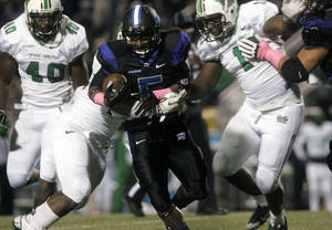 Photo - Middle Tennessee running back Jeremiah Bryson, center, rushes against Marshall in the second quarter of a college football game in Murfreesboro, Tenn., Thursday, Oct. 24, 2013. (AP Photo/The Daily News Journal, John A. Gillis)