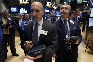 Photo - Trader James Denaro, center, works on the floor of the New York Stock Exchange, Monday, April 7, 2014.  Stocks are starting out the week the same way they ended the last one, down. (AP Photo/Richard Drew)