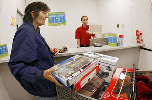 Photo - Customer Renee Pelham, of Oklahoma City, unloads items from her shopping cart in the layaway department at the Kmart store on N Harrison in Shawnee, in October 2008. PHOTO BY JIM BECKEL, THE OKLAHOMAN ARCHIVES